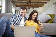Couple sitting in living room, using laptop, making an online payment with their credit card - BSZF00868