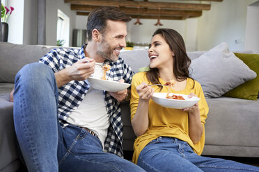 Couple sitting in living room, eating spaghetti - BSZF00871