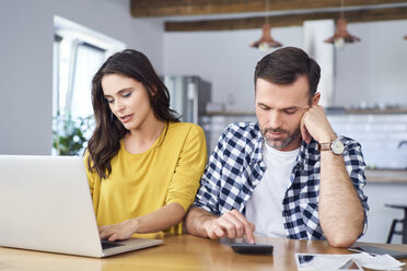 Worried couple sitting at dining table, using laptop, checking finances - BSZF00874