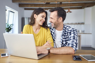 Couple sitting at dining table, using laptop, smiling - BSZF00877