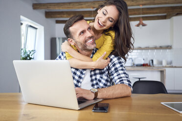 Happy couple sitting at dining table, embracing, using laptop - BSZF00880