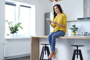 Woman sitting on kitchen counter at home, using digital tablet - BSZF00883