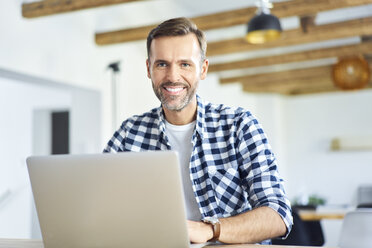 Portrait of man working remotely on laptop and looking at camera - BSZF00886