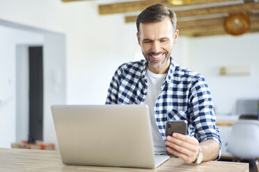 Cheerful man using phone while working on laptop at home - BSZF00889