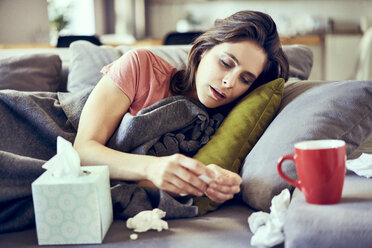 Portrait of sick young woman lying on covered in blanket trying to take pills for cold - BSZF00895