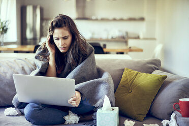 Sick woman trying to work from home on laptop - BSZF00898