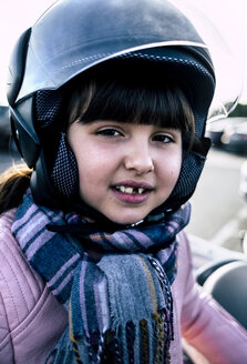 Portrait of little girl with tooth gap wearing helmet on motorcycle - MGOF03926