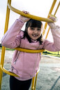Portrait of girl with tooth gap wearing pink leather jacket on playground - MGOF03929
