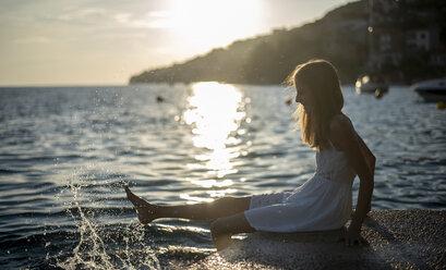 Croatia, Lokva Rogoznica, girl sitting at waterside during sunset splashing with water - BFRF01959