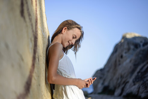 Croatia, Lokva Rogoznica, smiling girl leaning against rock looking at cell phone - BFRF01968