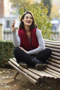 Portrait of smiling young woman relaxing with coffee to go on a bench - JSMF00729