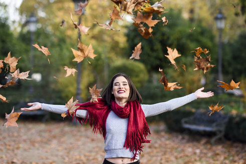 Portrait of laughing young woman with red scarf throwing autumn leaves in the air - JSMF00732