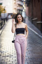 Portrait of smiling young woman with camera walking on the street - JSMF00738