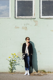 Female photographer leaning on wall - ASTF01279