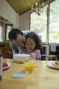 Affectionate father and laughing daughter at breakfast table - HEROF04104