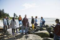 Beach cleanup volunteers on sunny beach rocks - HEROF04113
