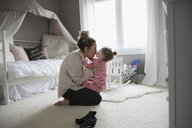 Affectionate mother kissing daughter on bedroom floor - HEROF04143