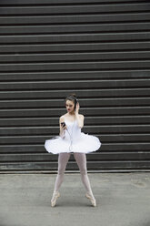 Ballerina in tutu listening to music with headphones and mp3 player in urban alley - HEROF04146