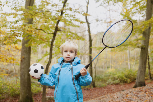 Portrait of boy holding badminton racket and ball in park - ASTF01322