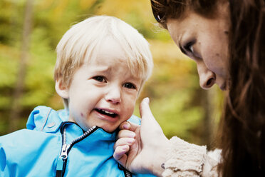 Boy crying while mother wiping tears - ASTF01334