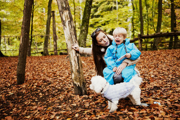 Woman looking at crying boy while sitting in forest - ASTF01337