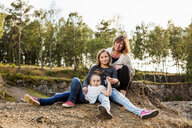 Portrait of mother sitting with daughters in forest - ASTF01397