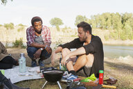Male friends barbecuing at lakeshore - ASTF01415