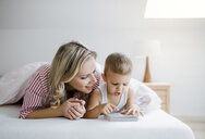 Smiling mother and toddler son lying in bed at home reading a book - HAPF02813