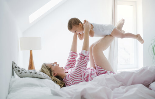 Happy toddler son playing with mother in bed at home - HAPF02819