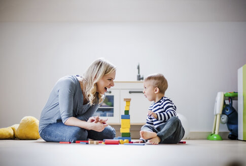 Happy mother and toddler son playing with building blocks at home - HAPF02828