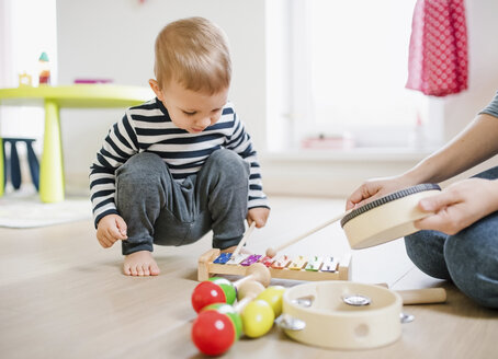 Mother and toddler son playing with musical instruments at home - HAPF02831