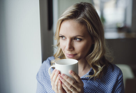 Smiling woman holding a cup of coffee at the window at home - HAPF02843