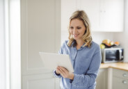 Smiling woman using tablet at home - HAPF02846