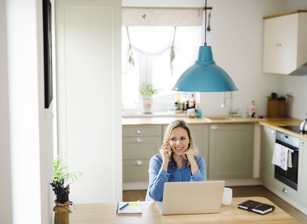Smiling woman with laptop and cell phone working at home - HAPF02855
