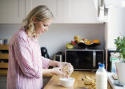 Woman preparing breakfast in the kitchen at home - HAPF02861