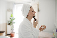 Smiling woman in bathrobe applying make-up in the morning at home - HAPF02873