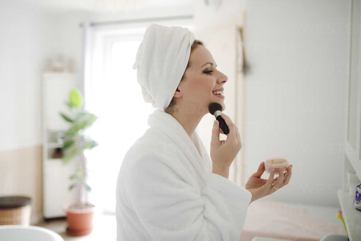 Smiling woman in bathrobe applying make-up in the morning at home - HAPF02873 - HalfPoint/Westend61
