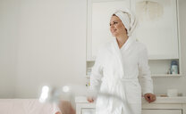 Smiling woman in bathrobe with towel around her head standing in bathroom at home - HAPF02876