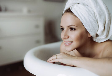 Smiling woman with towel around her head taking a bath at home - HAPF02879