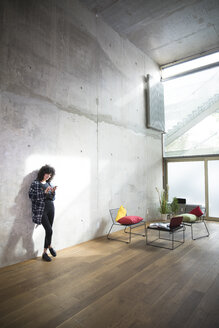 Woman leaning against concrete wall in a loft using cell phone - FKF03149