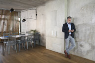 Businessman using cell phone leaning against concrete wall in a loft - FKF03167
