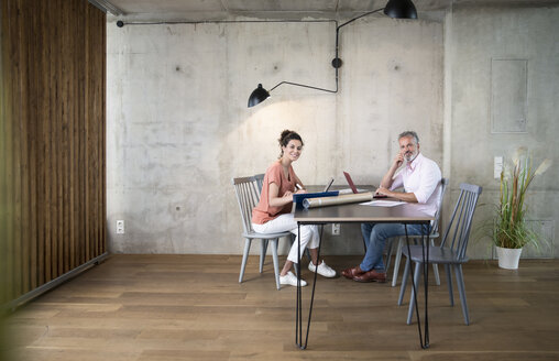 Smiling businessman and businesswoman working in a loft - FKF03170