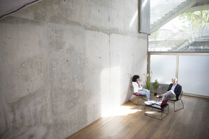 Businessman and businesswoman sitting in a loft at concrete wall - FKF03173