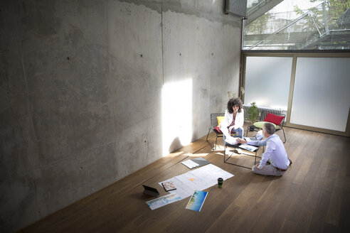 Businessman and businesswoman talking in a loft with documents on the floor - FKF03182