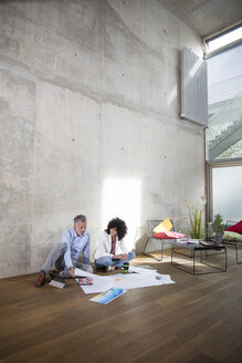 Businessman and businesswoman sitting on the floor in a loft discussing documents - FKF03185