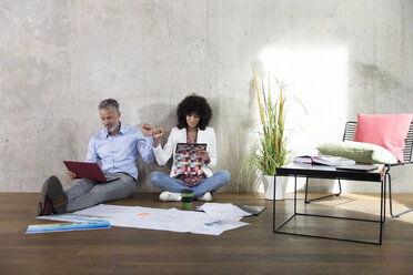 Businessman and businesswoman sitting on the floor in a loft using laptop and tablet - FKF03191