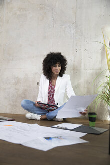 Businesswoman sitting on the floor in a loft working with tablet and documents - FKF03194