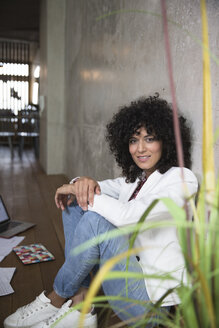 Portrait of smiling businesswoman sitting at concrete wall in a loft - FKF03200