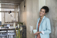 Portrait of smiling businesswoman holding coffee mug at concrete wall in a loft - FKF03203
