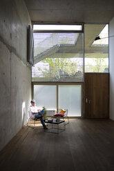 Businessman sitting in a loft at concrete wall having a break - FKF03209
